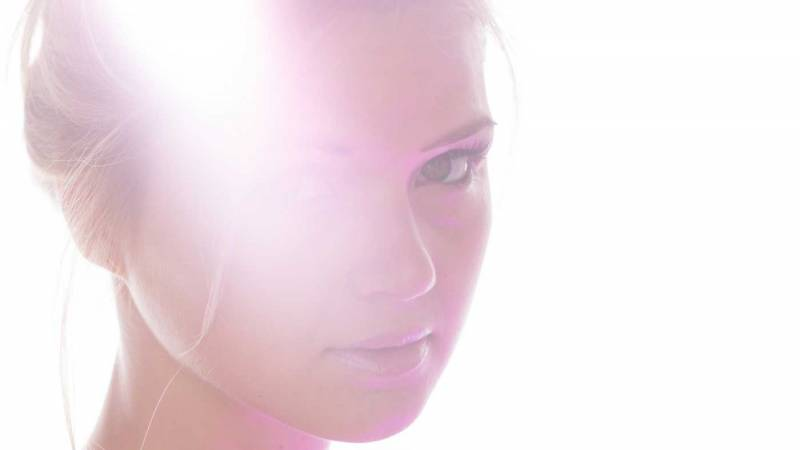 Portrait image of a woman with strong light flare across her face.