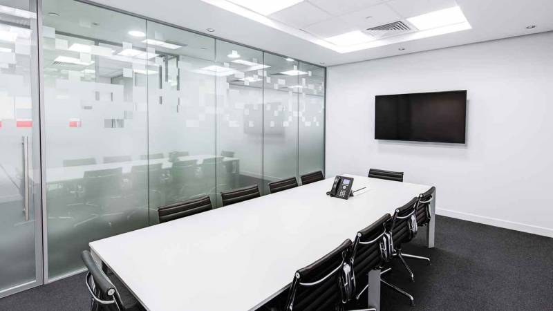 Photo of a modern office meeting room with lots of reflective surfaces.