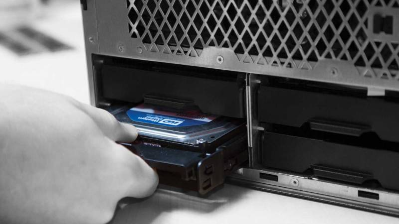 A person installing storage drive into a computer.