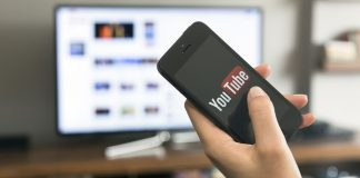 Hand holding a smartphone with YouTube's logo displaying on the screen