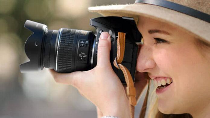 A smiling woman holding a Nikon camera