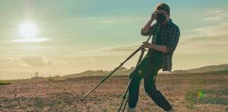 Man posing with a tripod in the desert