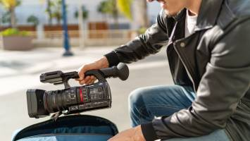 Filmmaker pulling out Panasonic AG-CX350 from bag