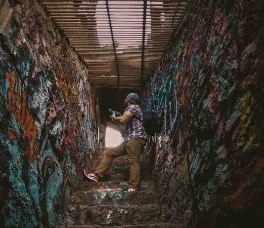 man with camera in a graffiti-ed stairwell