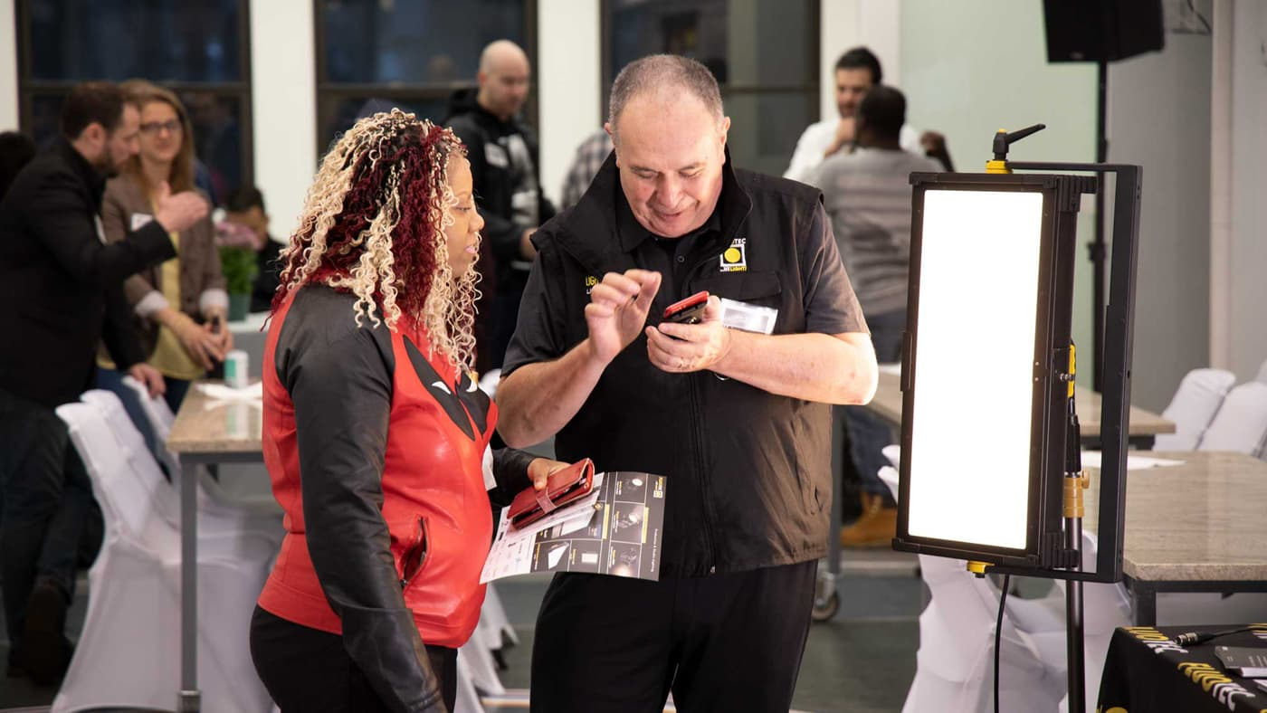 Man showing woman something on his smartphone at Videomaker's IRL meetup event