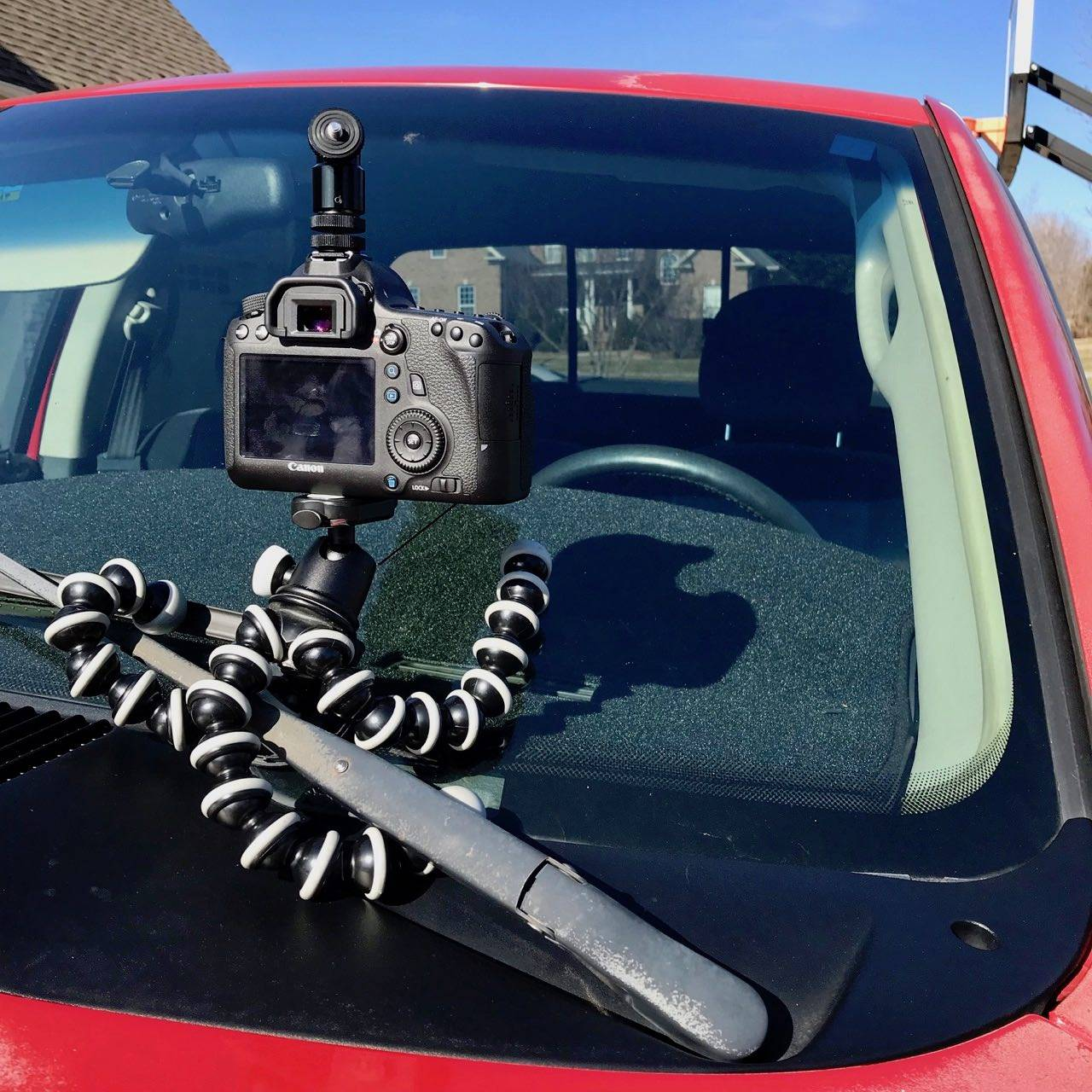 GorillaPod wrapped around vehicle's windshield wiper.