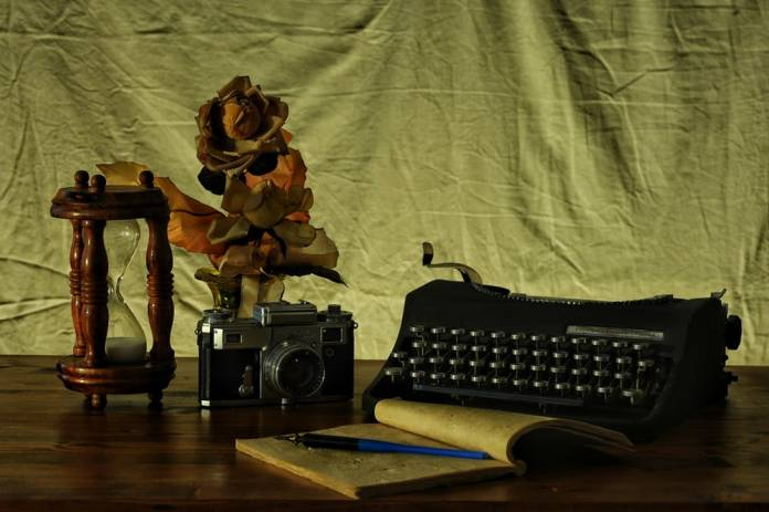 Typewriter with blank journal and 35mm camera