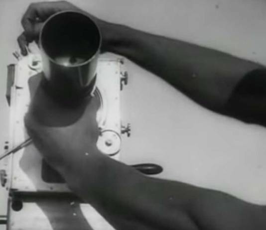 """Scene from """"Man with a Movie Camera"""" (1929) Hands adjusting a camera"""