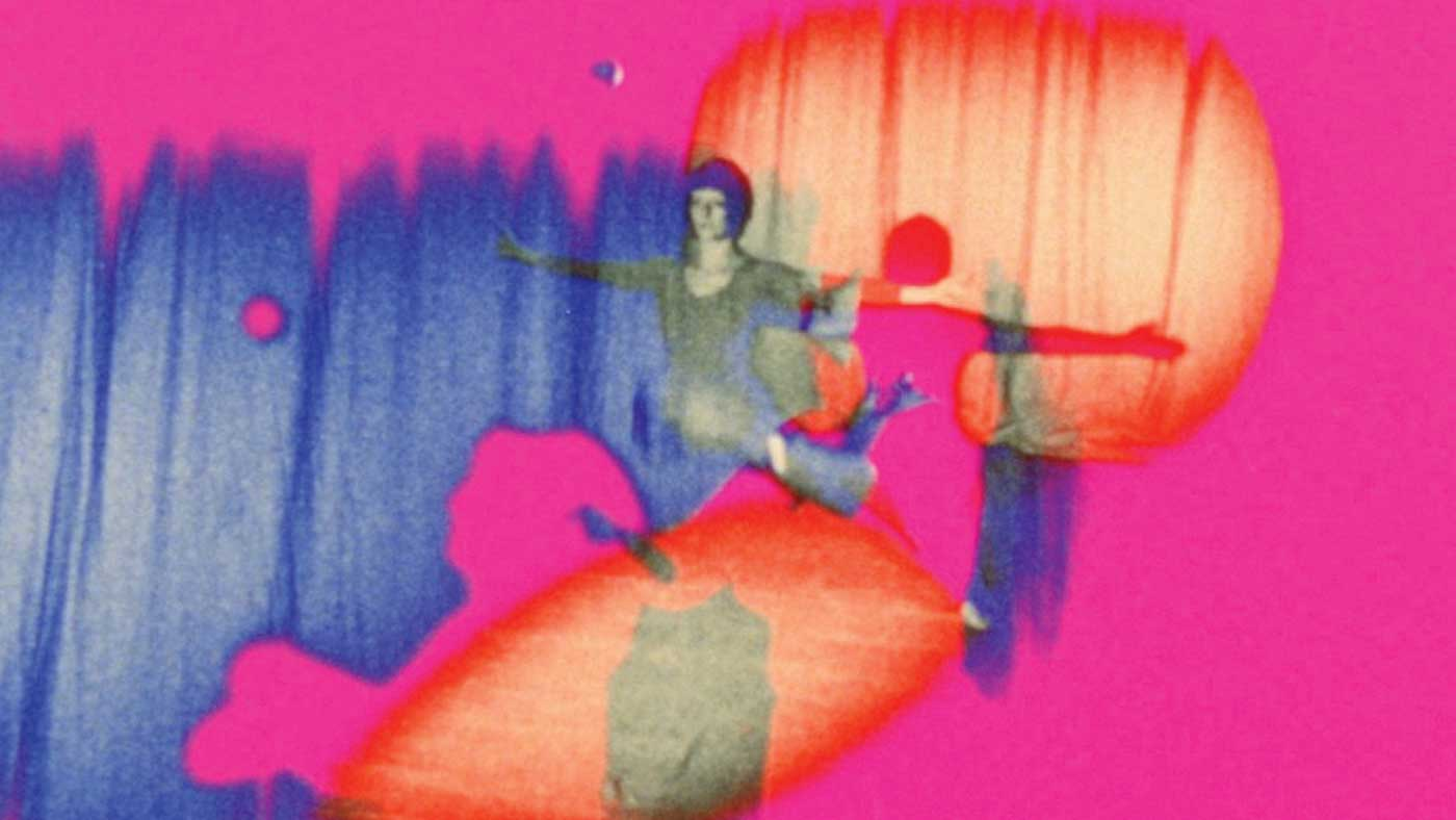 """Scene from """"Riddles of the Sphinx"""" (1977) Woman standing with out-stretched arms on pink and purple background."""