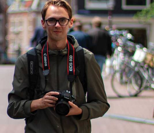 Man with camera in urban setting.