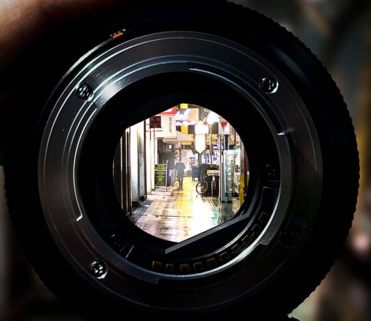 viewing a street scene through a detached lens at maximum aperture