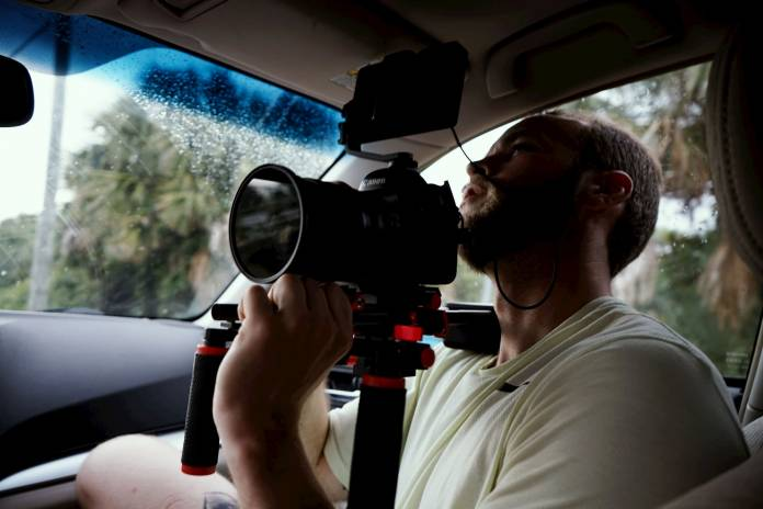 man holding a dslr camera in a vehicle