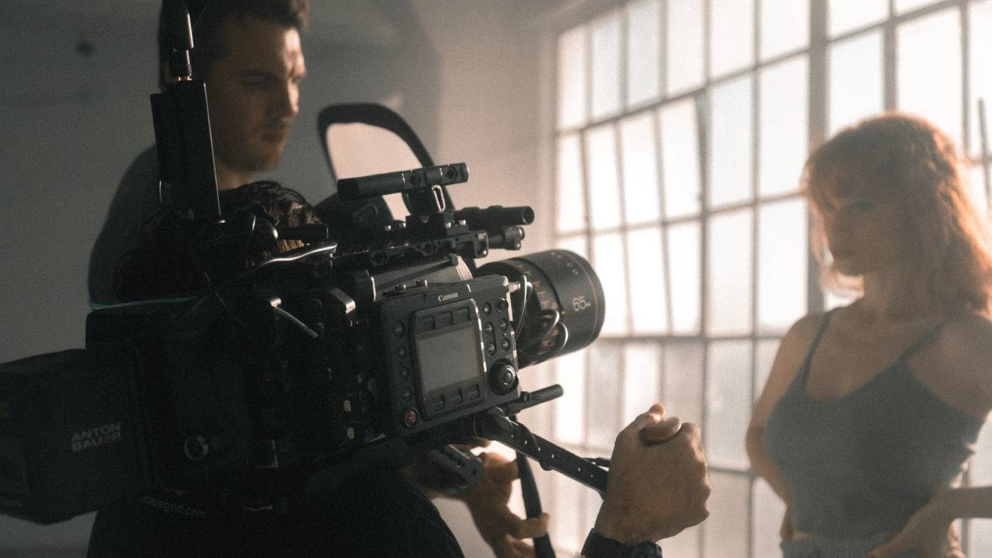 Director on set with camera operator and actress
