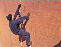 Vertical Angle: a man appearing to be climbing a red brick wall