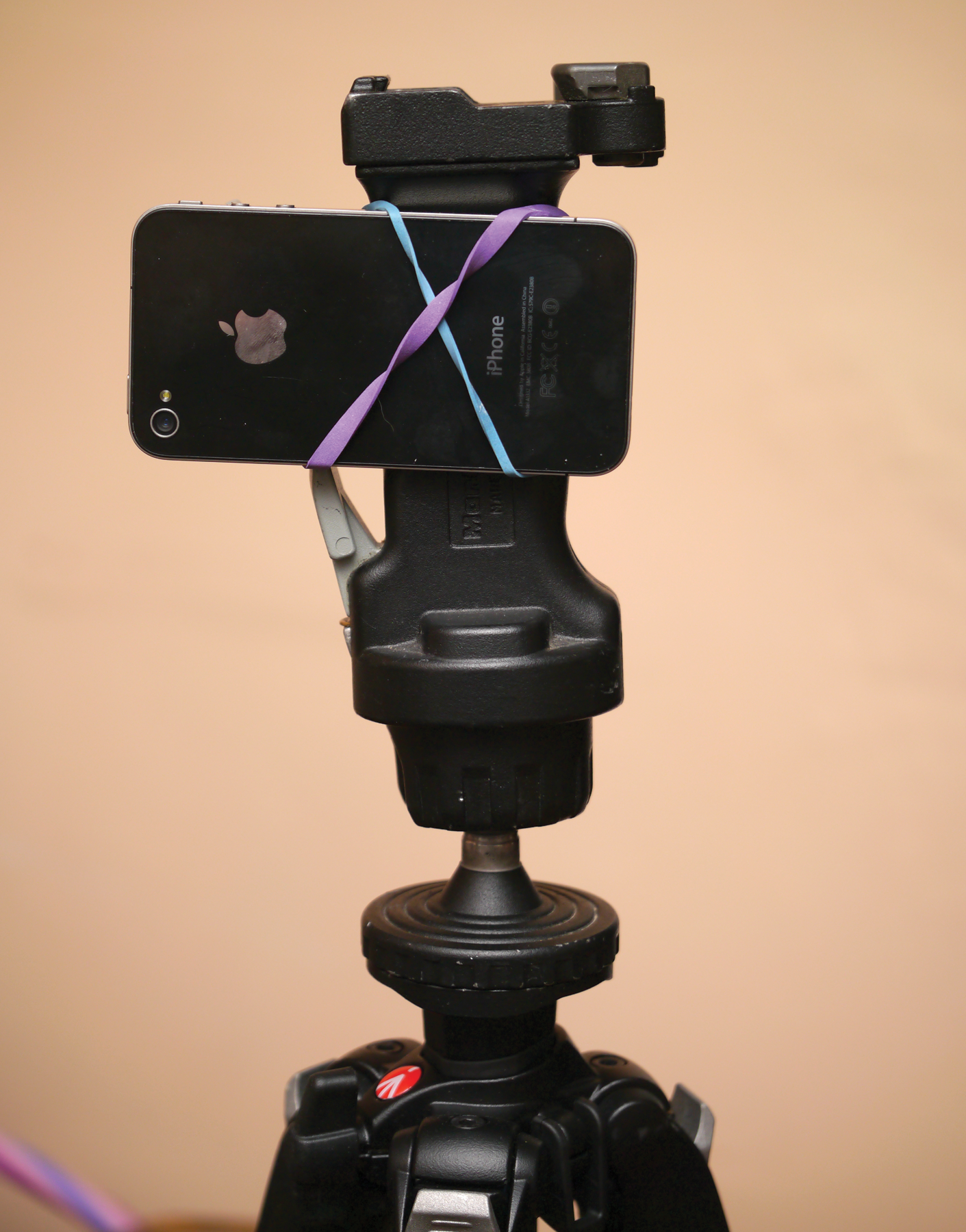 Shot of a professional tripod with an iPhone attached using two criss-crossed rubber-bands