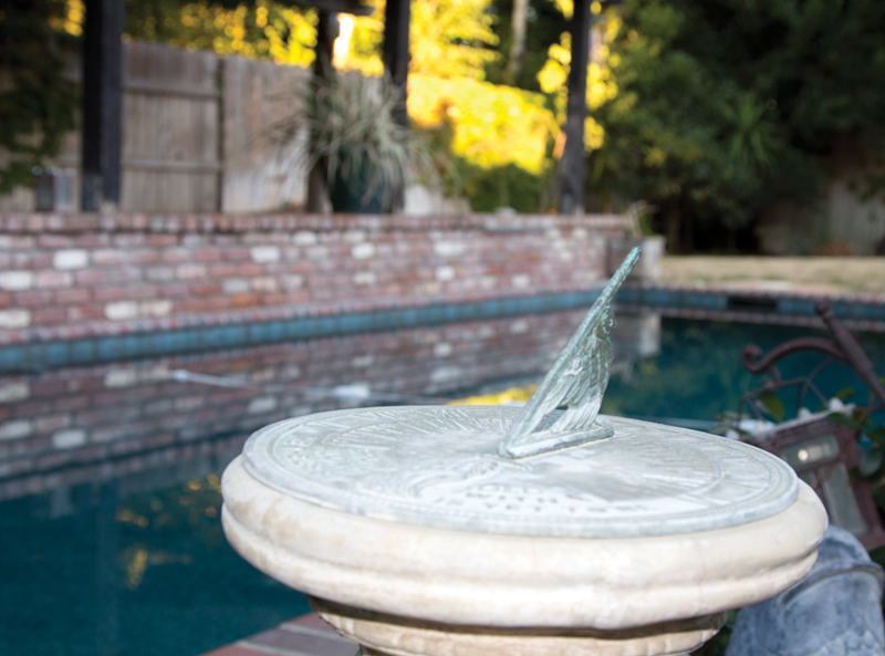 A sundial stands watch over a swimming pool.