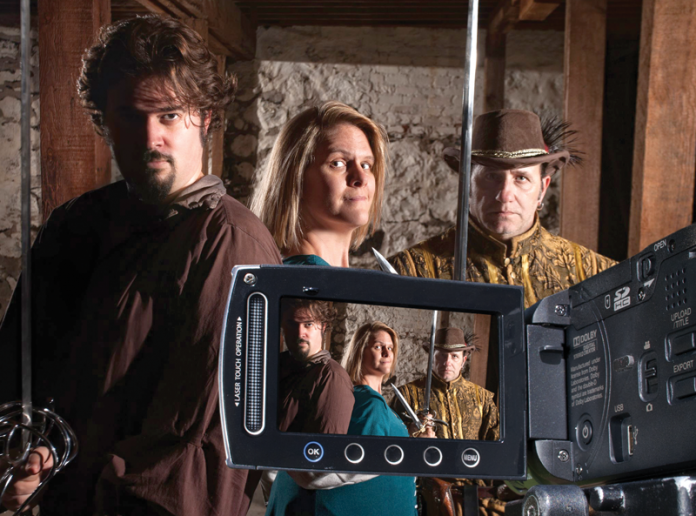 Three swashbuckling actors looking into a video camera