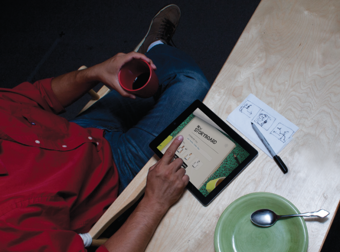 Man sitting at a desk with a storyboard drawn on a napkin that is recreated on a tablet using storyboarding software