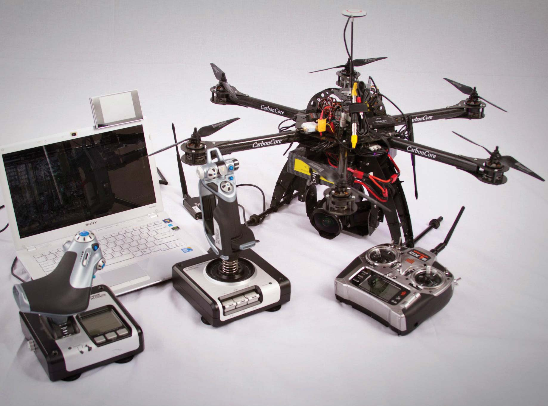 Collage of a CarbonCore drone helicopter with camera attached and the remote control units with a laptop as viewer.