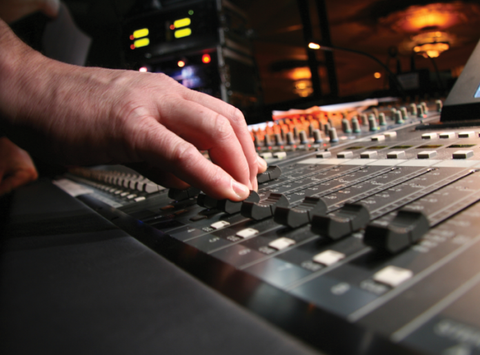 Closeup of hands on an audio mixing board at a live event