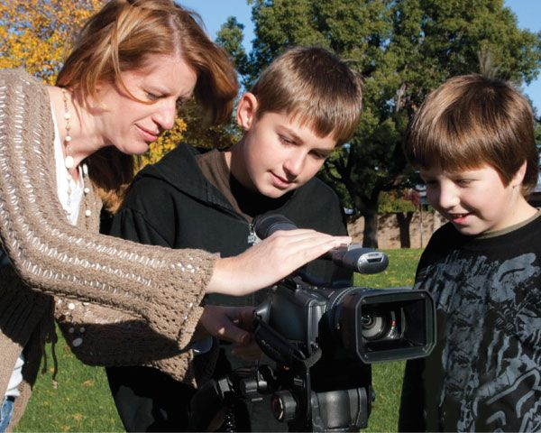 A woman and two boys operate a camera