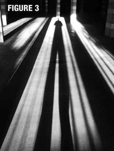Black and white photo of the long shadow cast by a person across a floor labeled, figure 3.