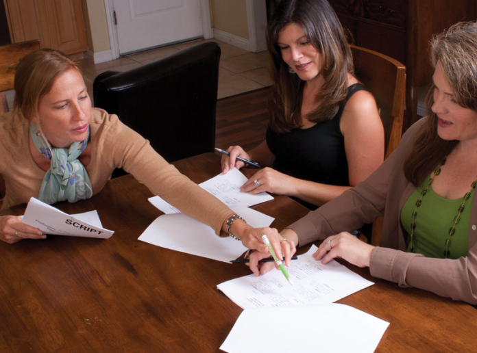 Three women at a table going over lines on a movie script