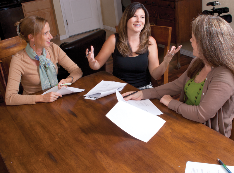 Three women at a table going over lines on a movie script. One woman is acting to another while the director offers suggestions.