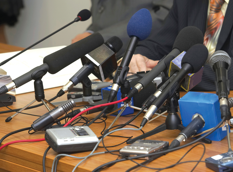 Assortment of microphone types at a news conference.