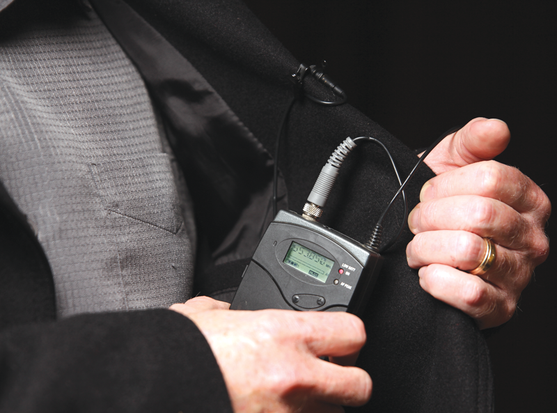 A groom placing the transmitter to a wireless mic system into his breast pocket, with the mic attached to his lapel