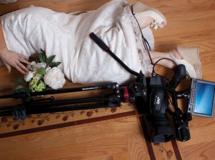 A camcorder on a tripod and a woman in a wedding dress laying on the floor. Cables are wrapped around the woman's legs.
