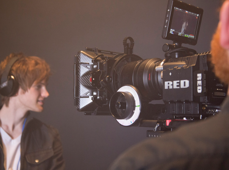 A RED camera mounted on a tripod with camera operator looking into the camera-mounted HD monitor.