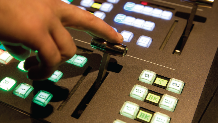 A hand is poised to make the switch using the t-bar of a switcher