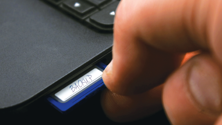 Person inserting an SD card into computer to back up files.
