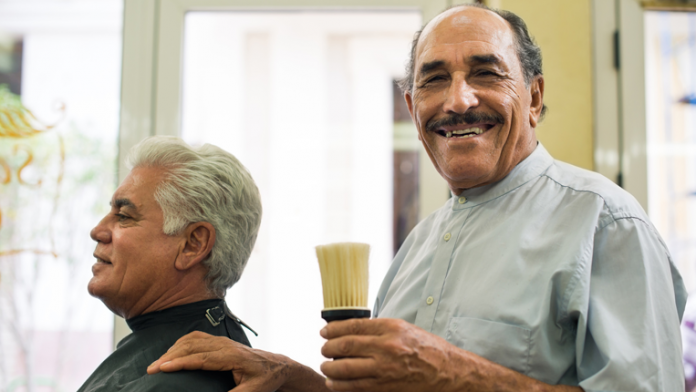 Barber in his shop with customer holding a shaving brush