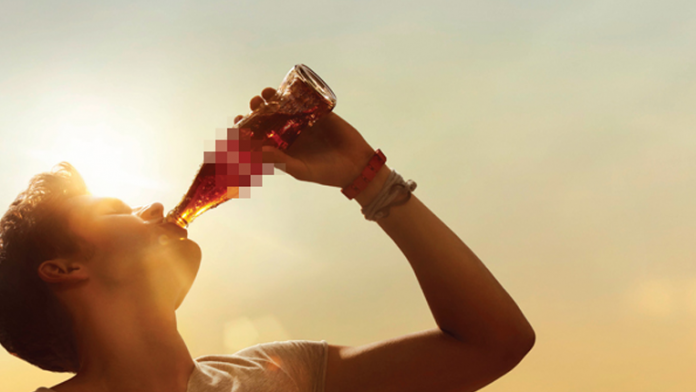 Person drinking cola with logo blurred out.
