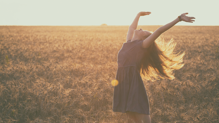 Girl spinning in a field with arms extended.