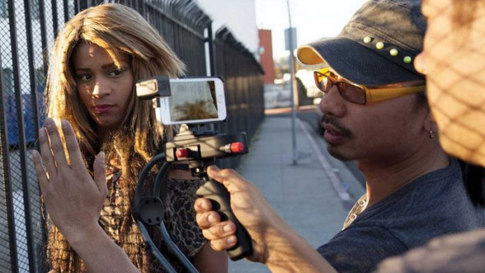 woman in front of smartphone on stabilizer with camera crew