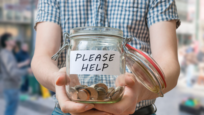 "Person with a donation jar with ""Please Help"" on it."