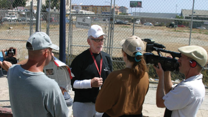 "Producer Patty Mooney and her husband/partner DP Mark Schulze interview Dave ""The Waterman"" Ross for their multi-award-winning documentary, ""The Invisible Ones: Homeless Combat Veterans"" (2008). A homeless man helps out by holding up a makeshift reflector. - Photo by Craig Gottshalk"