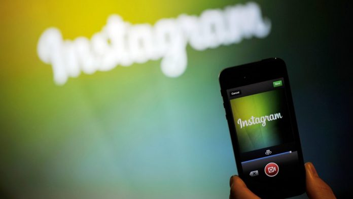 A smartphone filming a colorful background with the word Instagram on it