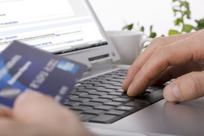 Credit card and laptop keyboard with person typing