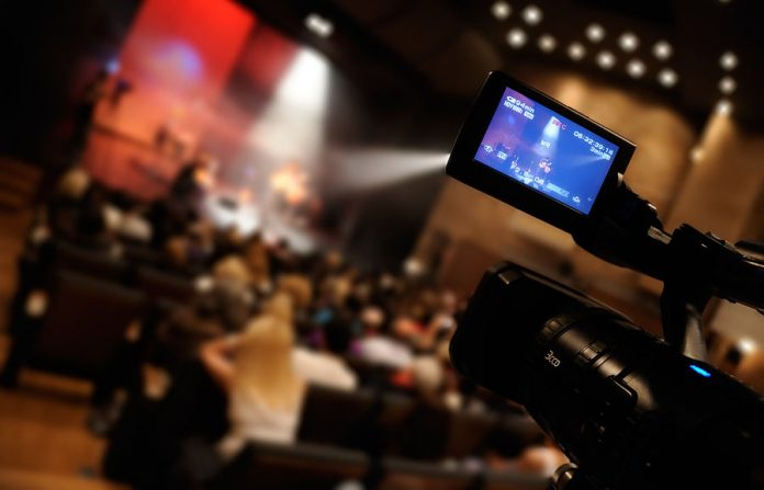 Video camera with viewfinder open at event.