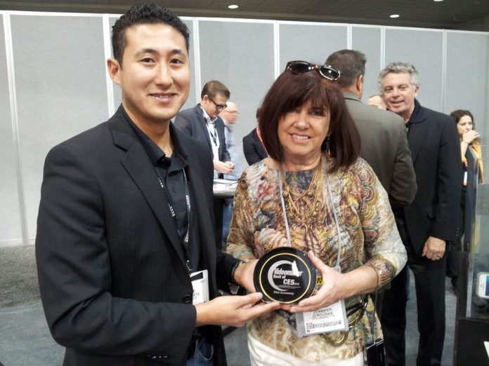 Two people at a tradeshow hold a plaque