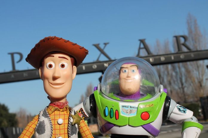 Toy cowboy and space ranger pose in front of a Pixar entrance