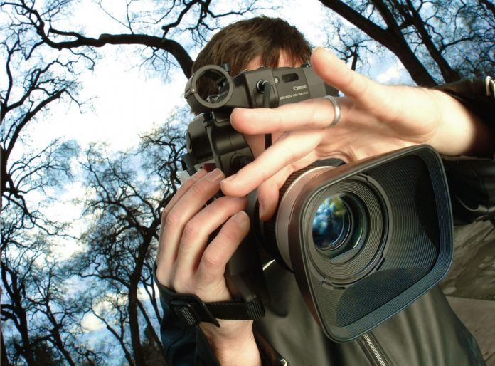 image of a man focusing a video camera