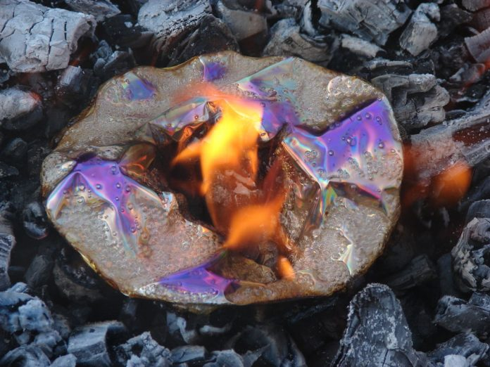 DVD is up in flame and melted on black coals