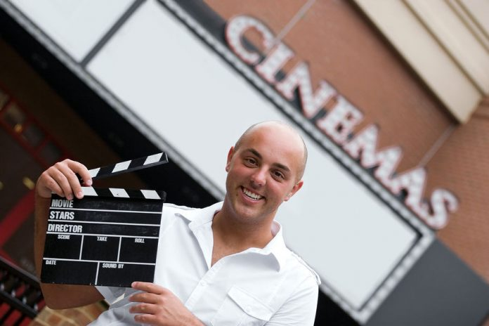 Image of a movie director holding a clapper card in front of a movie theater
