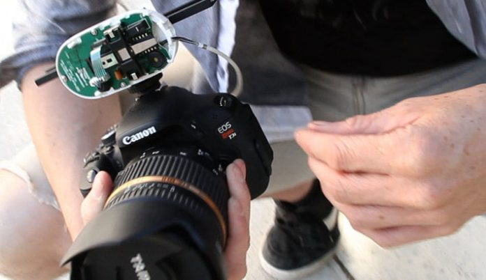 Canon DSLR with exposed device held by a person
