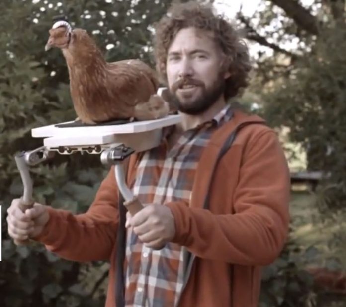 Shot of a man holding a camera stabilizing device upon which a chicken wearing a helmet camera sits.